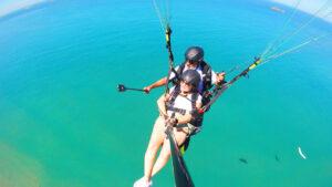 instrutor e cliente voando de parapente acima do mar azul do Rio de Janeiro