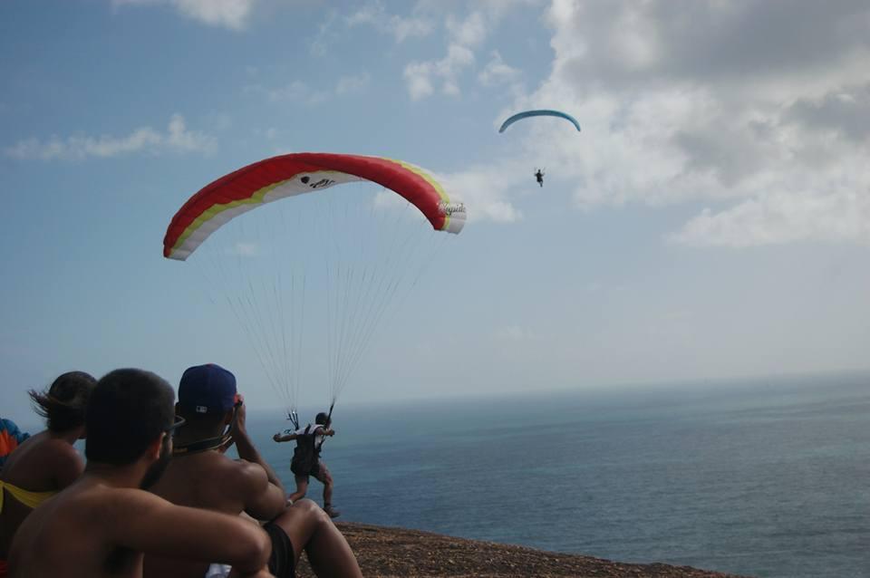 pessoas sentadas olhando dois saltos de parapente sendo realizados, mar ao fundo e céu azul com uma nuvem