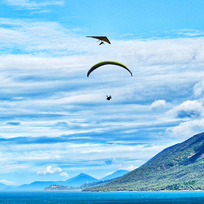 uma pessoa praticando o voo de asa delta e mais abaixo uma pessoa praticando o voo de parapente, um morro na direita compondo o fundo da imagem junto com o mar do Rio de Janeiro e o céu azul com nuvens